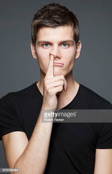 Young adult man picking nose