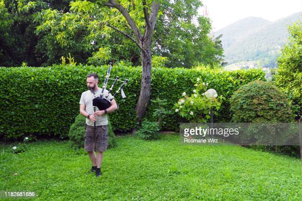 young adult man playing bagpipe in natural surroundings - bagpipes stock pictures, royalty-free photos & images