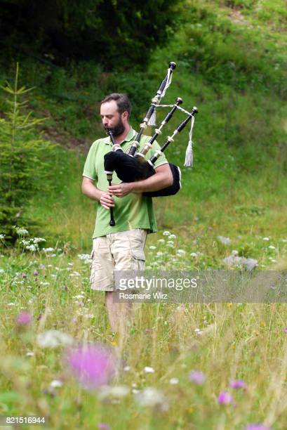 Young adult man playing bagpipe in natural surroundings