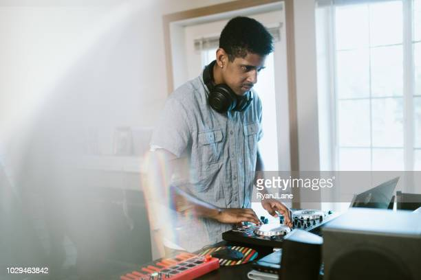 young adult man practicing his live dj set at home - producer stock pictures, royalty-free photos & images