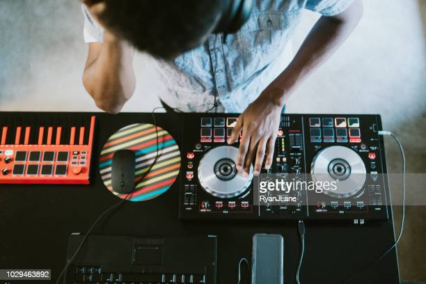 young adult man practicing his live dj set at home - dj stock pictures, royalty-free photos & images