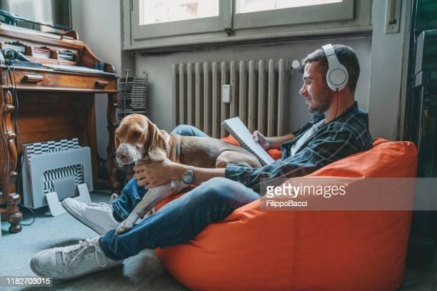 giovane adulto che legge e ascolta musica nella sua camera da letto con il suo cane - dog pad foto e immagini stock