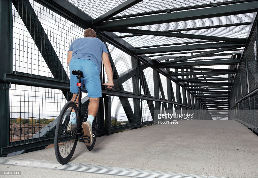 A young, adult man riding his bicycle on an urban bridge : Stock Photo