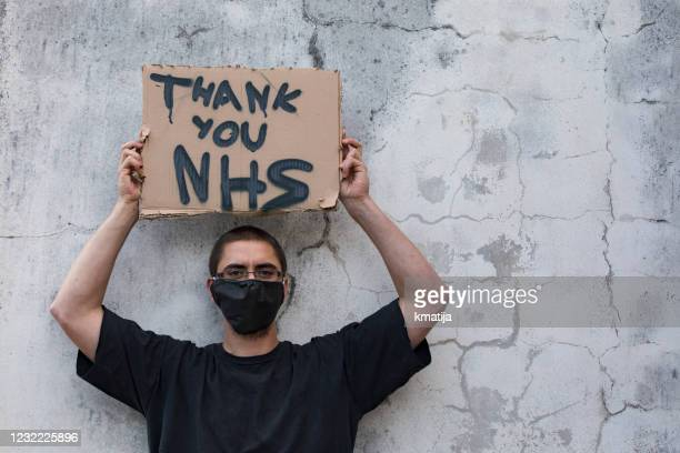young adult man showing gratitude and respect to nhs workers with carton sign outdoors on street - one man only stock pictures, royalty-free photos & images
