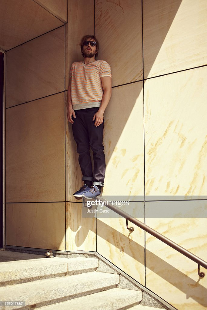 A young adult man standing on a stair-rail : Stock Photo