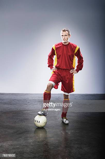 Young adult man standing with foot on soccer ball