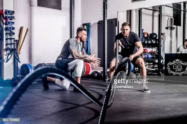 young adult man swinging ropes while fitness instructor motivates him - male friendship stock pictures, royalty-free photos & images