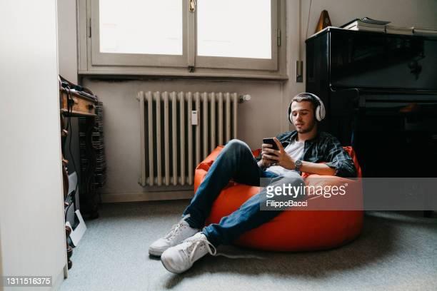 jeune homme adulte textos et écoutant la musique dans sa chambre à coucher - sacco photos et images de collection