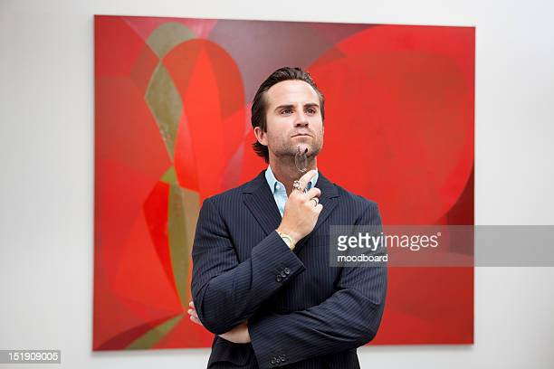 Young adult man thinking in front of painting in art gallery