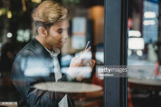 Young adult man using a smart phone behind a window shop