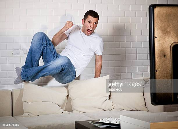 young adult man watching football on television: goal! - fan enthusiast stock pictures, royalty-free photos & images