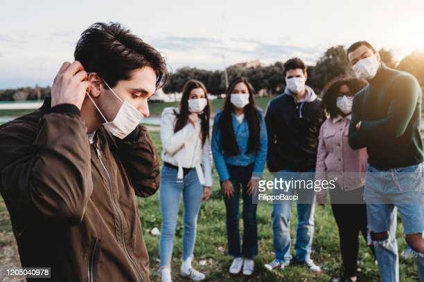 young adult man wearing a pollution mask to protect himself from viruses. his friends are in the background. - italy coronavirus stock pictures, royalty-free photos & images