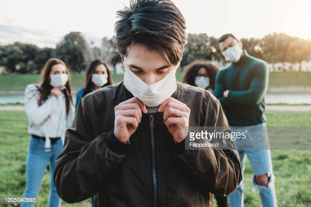 young adult man wearing a pollution mask to protect himself from viruses. his friends are in the background. - coronavirus imagens e fotografias de stock