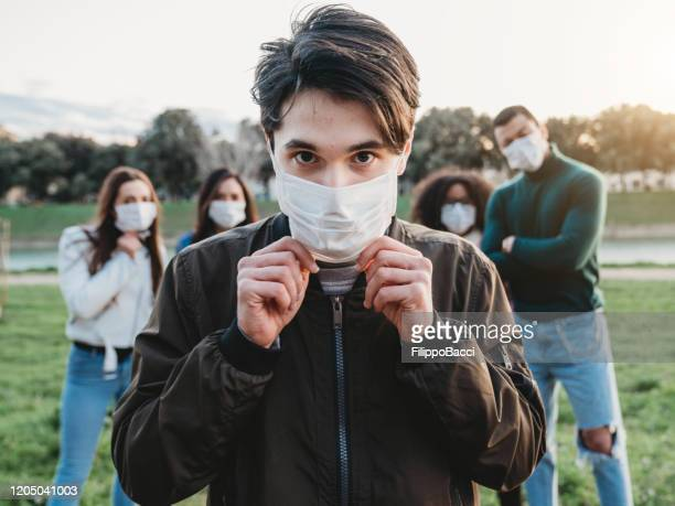 young adult man wearing a pollution mask to protect himself from viruses. his friends are in the background. - adolescence stock pictures, royalty-free photos & images