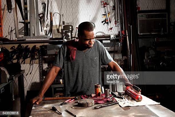 Young adult mechanic in small business repair, workshop.