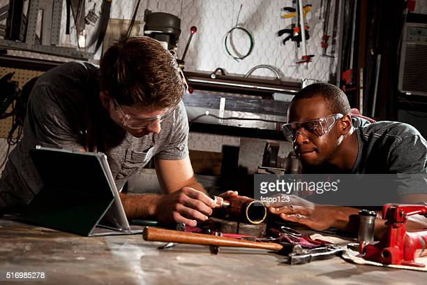 Young adult mechanics in small business repair, workshop. Digital tablet.