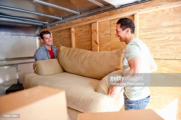 Young Adult Men lifting a couch in moving truck