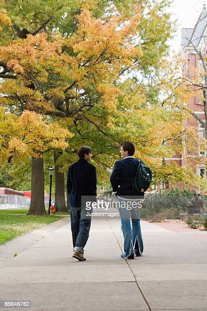 Young adult men walking on college campus