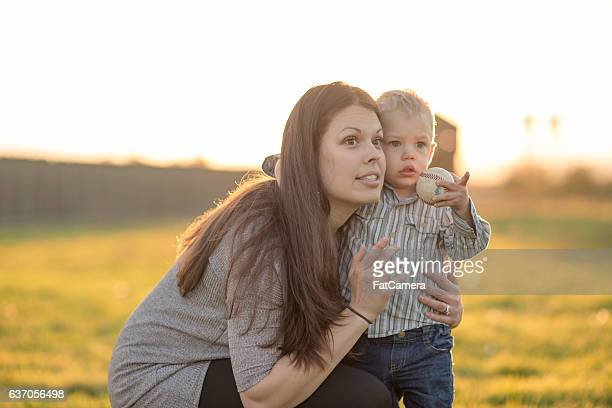 Young adult mother hold her toddler son in a park