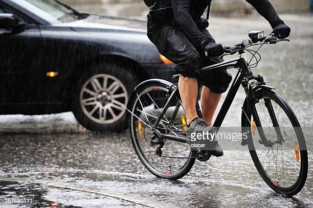 Young adult on bike in the city, rainy evening traffic