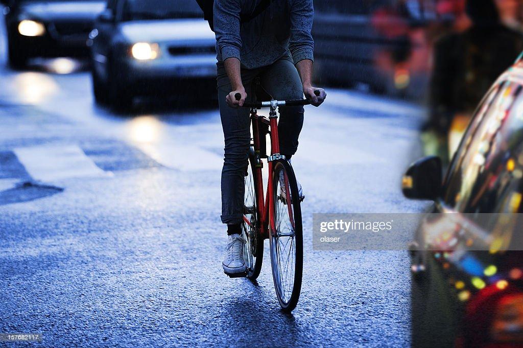 Jeune adulte à vélo dans la ville, quel que soir trafic : Photo