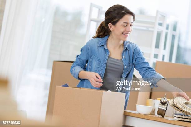 Young adult packs or unpacks a box in an apartment