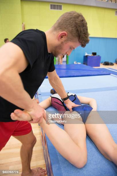 young adult physical therapist performing therapy on young gymnastics athlete - sports medicine stock pictures, royalty-free photos & images