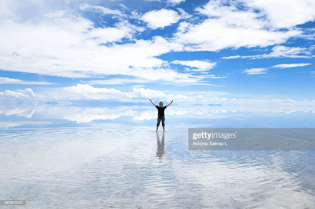 A young adult posing on the Uyuni Salar, the sky is reflected.