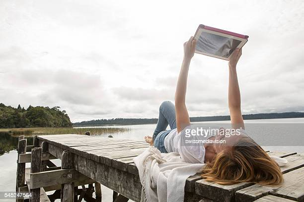 Young adult relaxes on jetty above lake, uses digital tablet