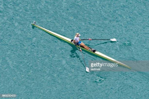 Young adult rowing woman practicing, single scull