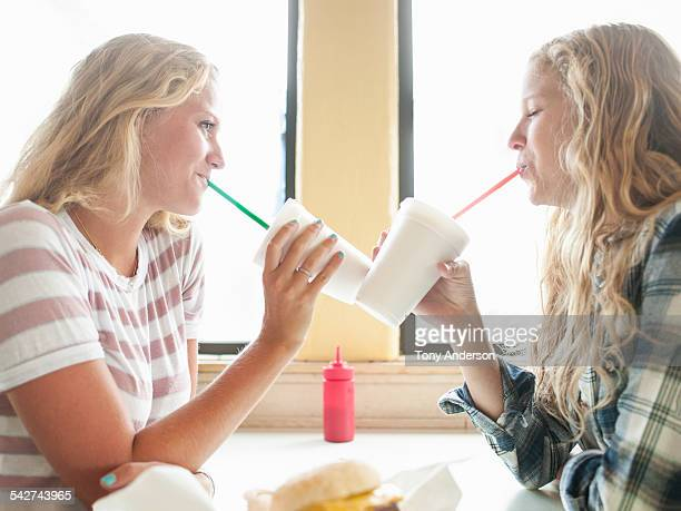 Young adult sisters in cafe with beverages and foo