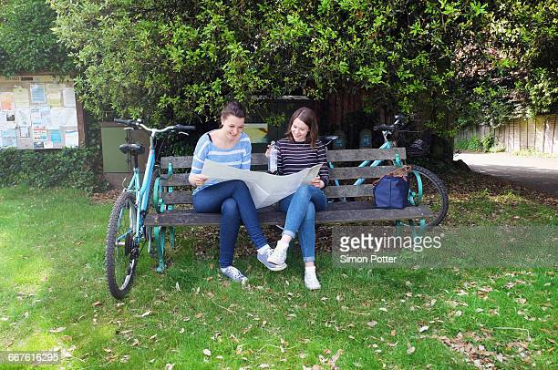 Young adult sisters with bicycles sitting on bench looking at map
