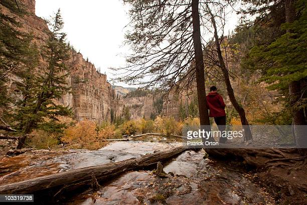 A young adult stands on the edge of a waterfall overlooking a canyon in Colorado.