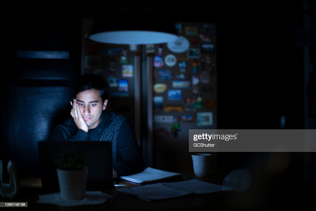 Young Adult Studying late in the Kitchen : Stock Photo