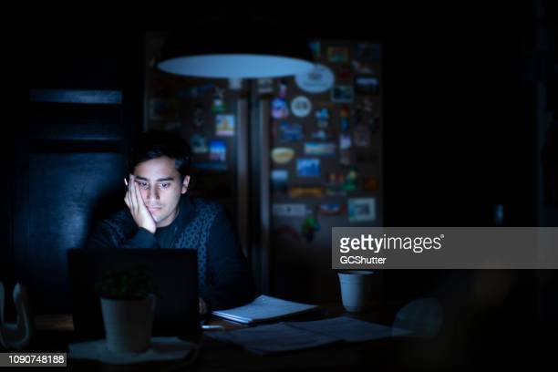 young adult studying late in the kitchen - midnight stock pictures, royalty-free photos & images