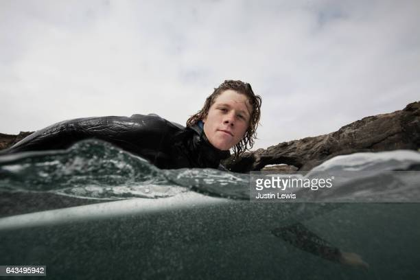 Young adult surfer, bare-headed, wearing winter wetsuit, paddles through rocks to find another perfect wave on a cloudy California morning