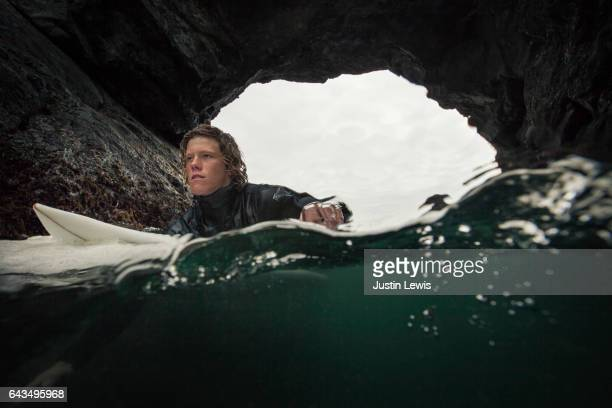 Young adult surfer, his hair wild and tangled, floats inside a sea cave, ready to paddle out into the wild morning surf, determined to test himself against whatever nature throws at him