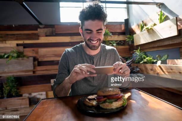 jovem adulto tirando uma foto do seu jantar para postar em seus meios de comunicação sociais - postando - fotografias e filmes do acervo