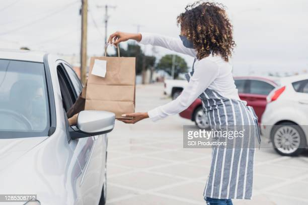 young adult waitress, wearing mask, social distances to deliver meal - curbside pickup stock pictures, royalty-free photos & images