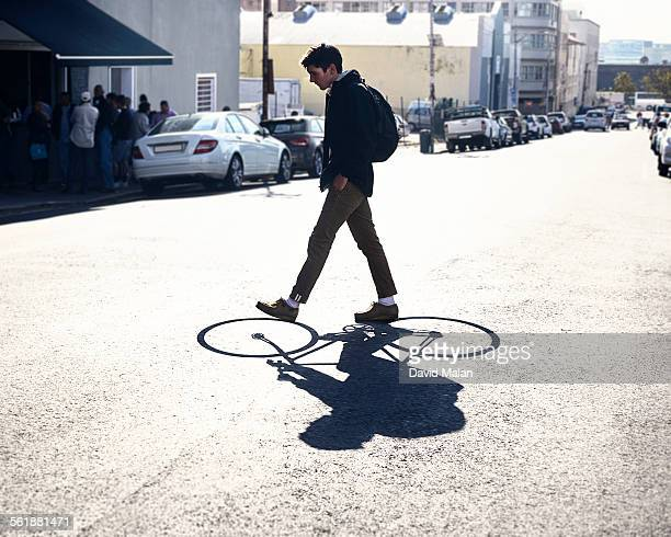 Young adult walking with a cycling shadow