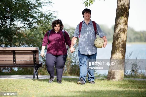 adulto joven con síndrome de down jugar caminando en un parque público - discapacidad intelectual fotografías e imágenes de stock