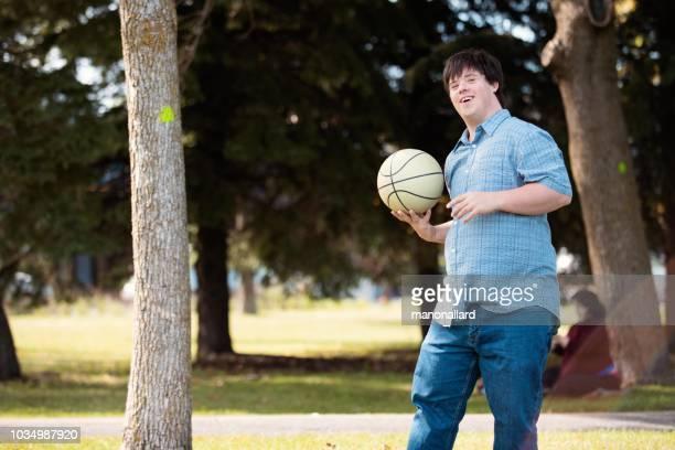 adulto joven con síndrome de down jugando con una pelota de basket - discapacidad intelectual fotografías e imágenes de stock