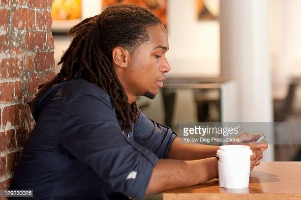 Young Adult with smartphone and coffee
