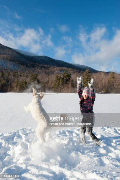 Young Adult Woman and Dog Playing in the Snow