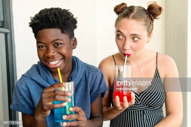 Young adult woman and teenage boy using paper straw.