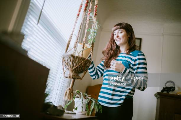 young adult woman at home watering plants - hanging basket stock pictures, royalty-free photos & images