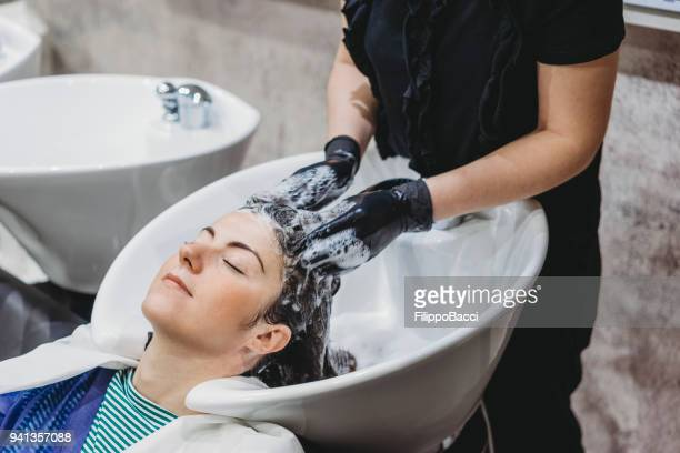 young adult woman at the hairdresser - hair conditioner stock photos and pictures