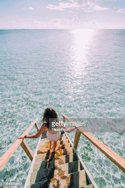 young adult woman chasing the sun in maldives - idyllic stock pictures, royalty-free photos & images