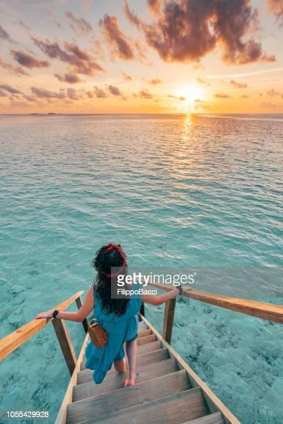 jovem adulta, perseguindo o sol nas maldivas - idílico - fotografias e filmes do acervo