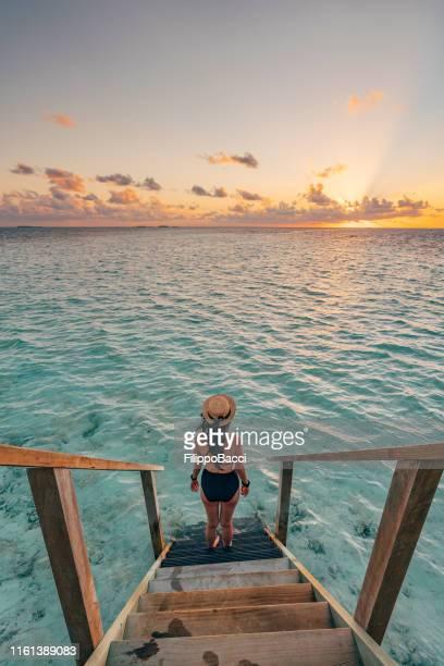 jonge volwassen vrouw die de zon achtervolgt in de malediven - tropical tree stockfoto's en -beelden
